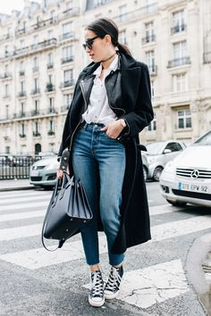 Alexandra Guerain wears a pair of sixties classic ankle high converse with cropped mom jeans and a simple white blouse, combined with layered black jackets to get that authentic style. Blouse/Jacket: Asos, Jeans: Levi's, Shoes: Converse.