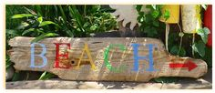Colorful driftwood beach signs by Art and Sand. Cottage featured on Beach Bliss Living: http://beachblissliving.com/cottage-in-red-blue-yellow/