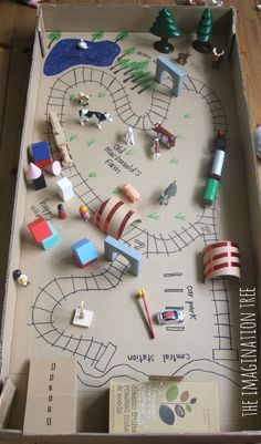 Cereal box train station, cardboard tube tunnels and train tracks drawn with markers in giant cardboard box!