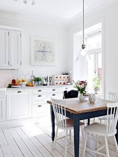 An all-white kitchen with a reclaimed wooden table.