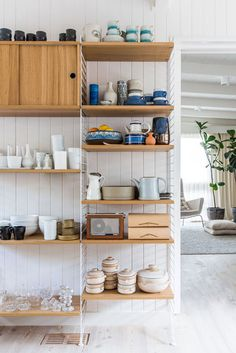 Organizing ceramics and glassware by color on open shelving delivers a more streamlined aesthetic.