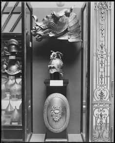 The Metropolitan Museum of Art, Arms and Armor Galleries; View of case display with (from top to bottom): Shaffron (horse's head defense) (04.3.253), Portions of a crinet (horse's neck defense) (04.3.254), helmet in the clasical style (04.3.259), and shield in the classical style (04.3.260). Photographed in 1907.