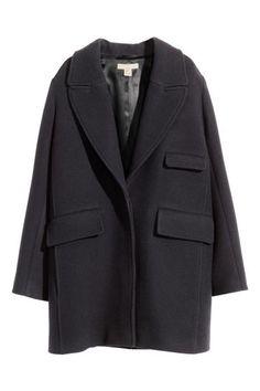 Manteau en laine mélangée: Manteau ample en laine mélangée. Modèle avec larges revers et boutonnage dissimulé devant. Poches latérales et poche de poitrine à rabat. Poche intérieure boutonnée. Doublé.