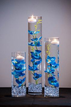 This Table Setting will include the following : 1 - 20 x 4 Cylinder Vase 1- 14 x 4 Cylinder Vase 1- 12 x 4 Cylinder Vase 3-Blue Orchids Silk Floral Strands (not real silk) 3- Floating Candles 1- Bag of Acrylic Crystals Want the flowers only?! They can be purchased here: #WeddingCenterpieceRustic