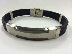Black and silver toned stainless steel bracelet with rubber strap. Approx 8.25 inches.  Priced at $68.