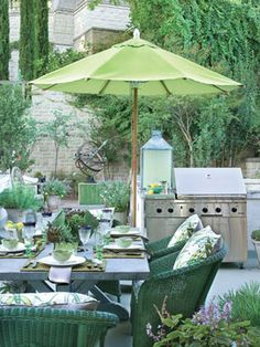 Stylish furnishings include iron seating, a zinc-top dining table and wicker dining chairs. A Dacor grill stands ready for alfresco cooking and entertaining in this green retreat.