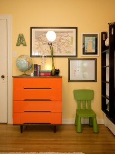 This shared kids' bedroom features a secondhand midcentury modern dresser and local artwork including a subway map of NYC and a hand-drawn sketch of the Empire State Building.