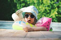 Little girl relaxes in a pool with floaties and sun protection by Lucas Saugen #stocksy #realstock