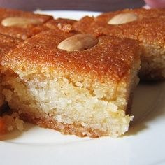 Basbousa is a sweet semolina cake soaked in syrup. Ingredients: cup butter – unsalted cup sugar 1 tspn vanilla essence 2 eggs 2 cups fine semolina (suji) 1 tspn baking powder tspn soda-bicarbonate cup plain or vanilla-flavored yogurt Egyptian Desserts, Egyptian Food, Egyptian Recipes, Middle East Food, Middle Eastern Desserts, Just Desserts, Delicious Desserts, Yummy Food, Comida Armenia