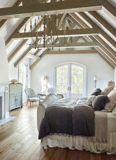 Elegant attic bedroom with exposed wood beam ceiling, wood floor, fireplace, sitting area and balcony.