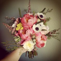 Wild wedding bouquet with coral peonies, anemones, astilbe, silver brunia and yarrow