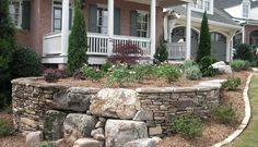 This beautiful front yard retaining wall of mixed stones makes a nice level area for a perennial bed.
