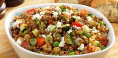 Freshly cooked quinoa mixes with chopped zucchini, red bell pepper, scallions, feta cheese, peas, balsamic vinaigrette and a touch of curry in this salad.