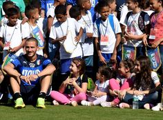Leonardo Bonucci of Italy poses with the students of the school...