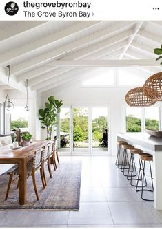 open white and wood dining room with vaulted ceilings and glass doors #beachhousedecorkitchen