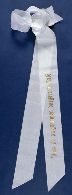 Anonymous | Lint 'Voor de omgekomen burgers in Azië', Anonymous, 2000 | Twee aan elkaar gebonden witte linten, gelegd op 4 mei 2000 bij het Nationaal Monument op de Dam. Het bovenste lint is v.z.v. een gouden opdruk. Onderste lint is blanco. Linten zijn aan de uiteinden schuin afgeknipt. Aan een zijde tot strik samengebonden met ijzerdraad. IJzerdraad gebogen t.b.v. bevestiging aan krans.