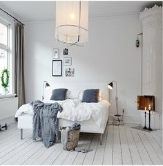Blue and white bedroom in Scandinavian style. Whitewashed floors and a Swedish stove (kakelugn) in the corner.