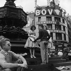 Selling newspapers from the steps of Eros, Piccadilly Circus, 1958. [Note the New  York Herald Tribune sweater a couple years before it was made famous by Jean Seaberg in Breathless (1960).]