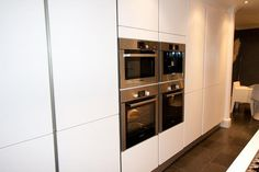 Tall white kitchen units with integrated appliances