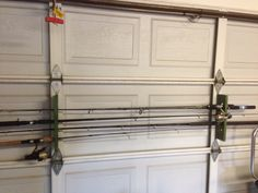 Fishing rod holder made from pallet wood and hung on the garage door. Easy to do with a kraig jig and a hole saw.