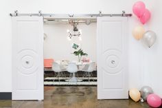 """These doors were one of Tina's standout design elements: """"I've never tried a barn door like we did for the conference room. Barn doors tend to be industrial but we took it to a totally different direction!  We chose doors that have round detailing and attached crystal door knobs to the center of the doors!   I think we achieved a really chic and unexpected entrance into the conference room!"""""""