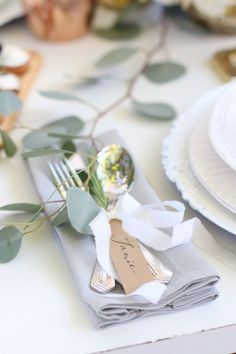 A cozy fall tablescape with tied cutlery and escort card.