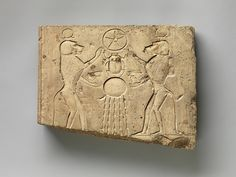 Relief panel showing two baboons offering the wedjat eye to the sun god Khepri, who holds the Underworld sign | Late Period–Ptolemaic Period | The Met