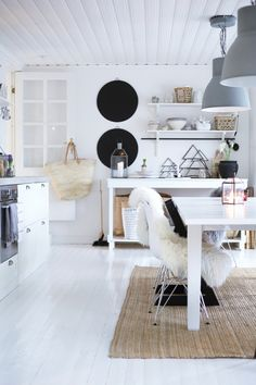 White kitchen, love the sheepskin over the chair and the natural rug