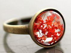 Echter Blüten Ring transparent II. Ring aus 100% Messing mit transparentem echten Blütenstein mit kleinen roten Blüten.   Der Ring wurde von uns oxidiert und versiegelt - er hat einen ganz dunklen vintage Bronzeton. Bitte beachten: Jeder Ring ist ein Unikat und sieht aufgrund der Blüten etwas anders aus.