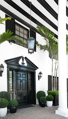 Painted black and white stripes under the patio; black door and shutters with a pop of green palms