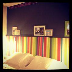 Cabeceira com tecido tamtum colorido e parede em preto
