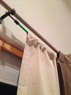 Used two 32'' bungee cords to hang the ugly thermal drapes behind the nice drapes, using the existing curtain rod brackets. Cost me $3. No more drafty sliding glass door!