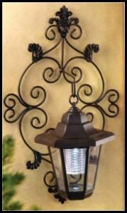 FREE SHIPPING Delicate scrollwork wall plate and classic hurricane lamp make a gracious addition to your outdoor living space; hidden solar collectors store sunlight for plentiful after-dark illumination. The perfect fusion of smart energy savings and old fashioned charm!Four solar panels on top of the lantern. Two holes on back for mounting. One AA 600mAh 1.2 V battery included.  Item: 14256