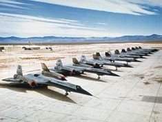 "All ten remaining A-12 aircraft parked at the Lockheed plant in Palmdale, California, after the Oxcart program was terminated. Second from the left is the dual-seated A-12, nicknamed the ""titanium goose,"" used to train A-12 pilots. It was never configured with J-58 engines. Lockheed Martin"