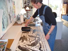Holly Meade at work in her printmaking studio, using a brayer to roll the ink onto her carved Lino-cut before printing it.