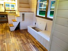 Stairs (with the washer-dryer combination and water heater underneath) and a couch with built-in storage in the Robins Nest tiny house see more at brevardtinyhouse.com