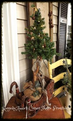 luv my goodwill finds! sweet lil tree with burlap base was once covered in pink ribbons and teddy bears. now i like her plain and simple wearing some rusty bells and a homespun tie. also found this perfect little twiggy sled to be her new home. xoxo