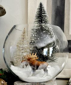 bottle brush trees, old plastic kiddie toys/ornament, white sand.. in a glass bowl.