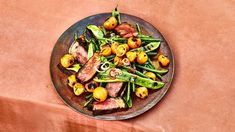 For this grilled strip steak recipe, cooking half the tomatoes in a skillet placed on the grill lets you capture all their juices and turn them into a saucy condiment.