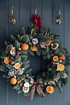 Large real Christmas wreath with dried oranges, pine cones, cinammon sticks and a tartan bow. Shown here against a panelled boot room wall painted in Farrow & Ball's Downpipe. Christmas Love, Christmas Holidays, Christmas Ideas, Christmas Tree Decorations, Christmas Wreaths, Holiday Decor, Room Wall Painting, Eucalyptus Garland, Dried Oranges