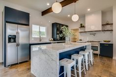 mid century modern home with beams and open spaces, hardwood floors, french doors, waterfall island