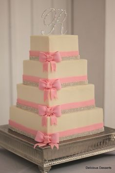 Inspired by a delicate pink bow invitation, this cake is decorated with fondant bands, gumpaste bows, & crystal