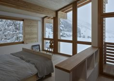 Rothaus | Jonathan Tuckey Design, Andermatt, Switzerland. A double height window frames the surrounding landscape, whilst opening up the internal space to create a light and spacious master bedroom. Engineered larch timber-frame structure, Larch joinery and walls finished in a natural white plaster.