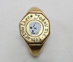 An important memento mori ring; gold with an octagonal bezel containing a black and white enamelled skull in the center around which in black enamel the tekst 'Today me, Tomorrow Thee' and on the inside a monogram A.T., England, 16th or 17th century.