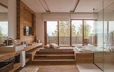A suíte do casal tem uma verdadeira sala de banho com terraço, com madeira de demolição na parte seca do piso e nas paredes. Um painel apoia a TV, que é vista da banheira. Para relaxar, há ainda um futon. Projeto da arquiteta Lica Cukier