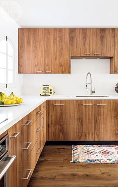 Walnut kitchen cabinetry with white counter and backsplash // mid century modern cabin design