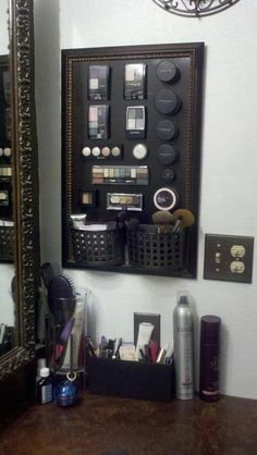 A picture frame painted with black magnetic paint. Make-up cases have a magnetic strip added to the back. Two small baskets have been attached too.