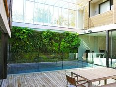 The design of this new home makes maximum use of the available space with this beautiful outdoor Fytowall by Ftogreen overhanging the swimming pool.