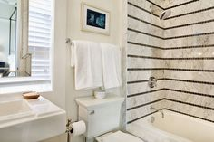 Beautiful bathroom features a rectangular pedestal sink with fretwork mirror mounted in front of the window beside toilet with towel rail and art above.