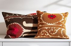 A pair of pillows made from hand-embroidered suzani tapestries.